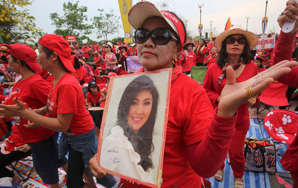 A pro-government Red Shirt member dances with a portrait of Thai Prime Minister Yingluck Shinawatra during a rally in Bangkok.
