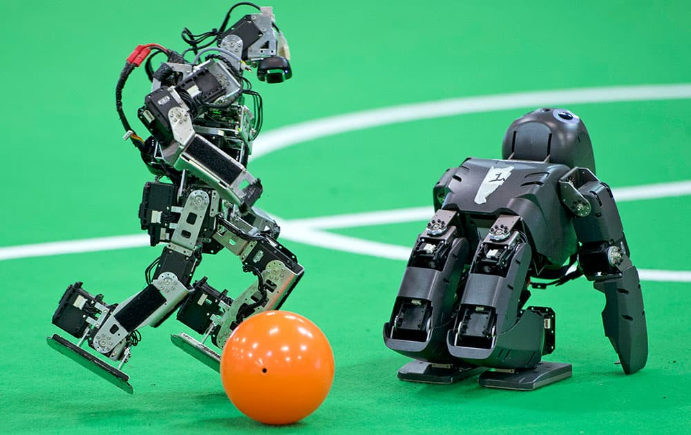 A robot of a German team, left, plays the ball besides a British team robot in the Kids League at the RoboCup German Open 2014 in Magdeburg, Germany.