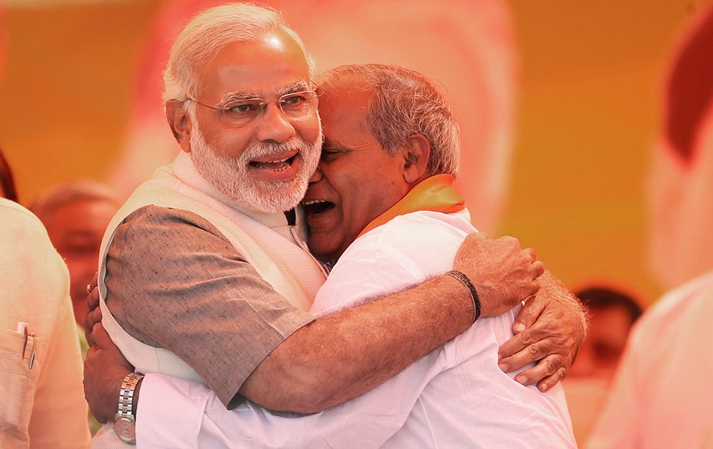 Narendra Modi is hugged by a party leader at an election rally in Vaishali, Ghaziabad.