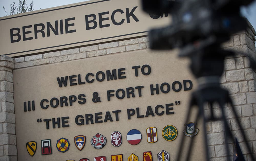 Members of the media wait outside of the Bernie Beck Gate, an entrance to the Fort Hood military base, for updates on a shooting that occurred inside in Fort Hood, Texas.