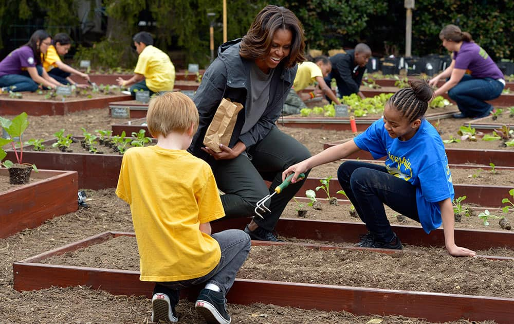 First lady Michelle Obama talks with Friendship Public Charter Elementary School student Dynasty Meade, center, and Bancroft Elementary School student Silas Stutz, left, as they plant Lincoln oats in the White House Kitchen Garden at the White House in Washington.