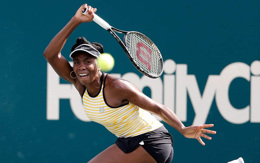 Venus Williams returns to Chanelle Scheepers, of South Africa, during the Family Circle Cup tennis tournament in Charleston, S.C.