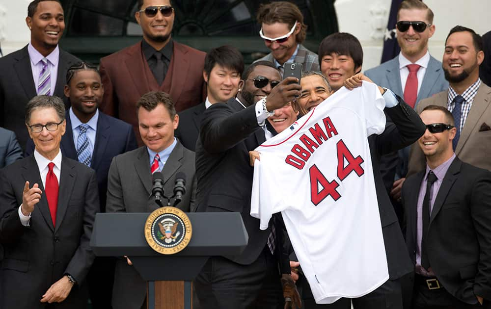 Boston Red Sox designated hitter David `Big Papi` Ortiz takes a selfie with President Barack Obama, holding a Boston Red Sox jersey, as the president Obama honored the 2013 World Series baseball champion Boston Red Sox.