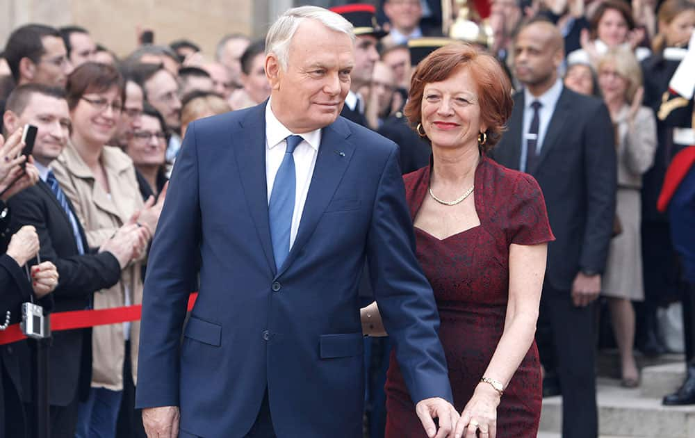 Outgoing French Prime Minister Jean-Marc Ayrault and his wife Brigitte leave after the takeover ceremony with new Prime Minister Manuel Valls, at the Prime Ministry in Paris.