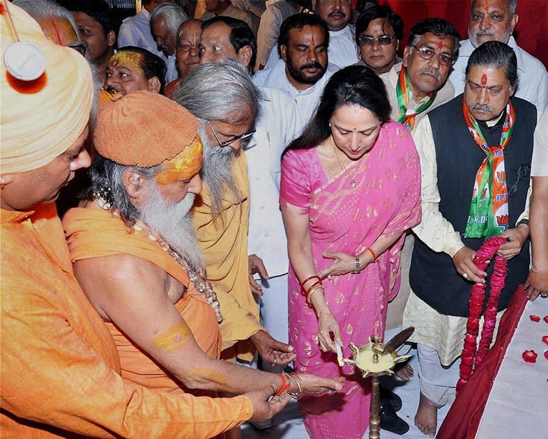 BJP Candidate and Bollywood actress Hema Malini lighting lamp along with priests during her election campaign in Mathura.