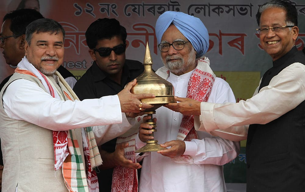 Prime Minister Manmohan Singh receives a traditional memento from Chief Minister of Assam state Tarun Gogoi and Congress party leader Bhubaneswar Kalita, during an election campaign rally at Khumtai, Assam.