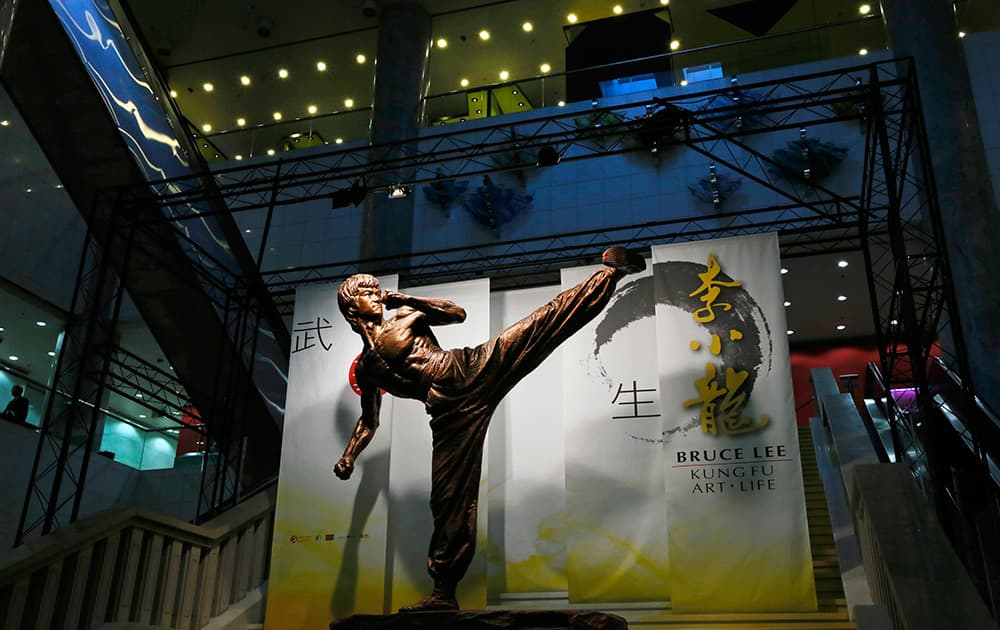 A man walks near a statue of pop culture icon Bruce Lee at Lee`s memorial exhibition at the Hong Kong Heritage Museum in Hong Kong, to mark the 40th anniversary of his death.