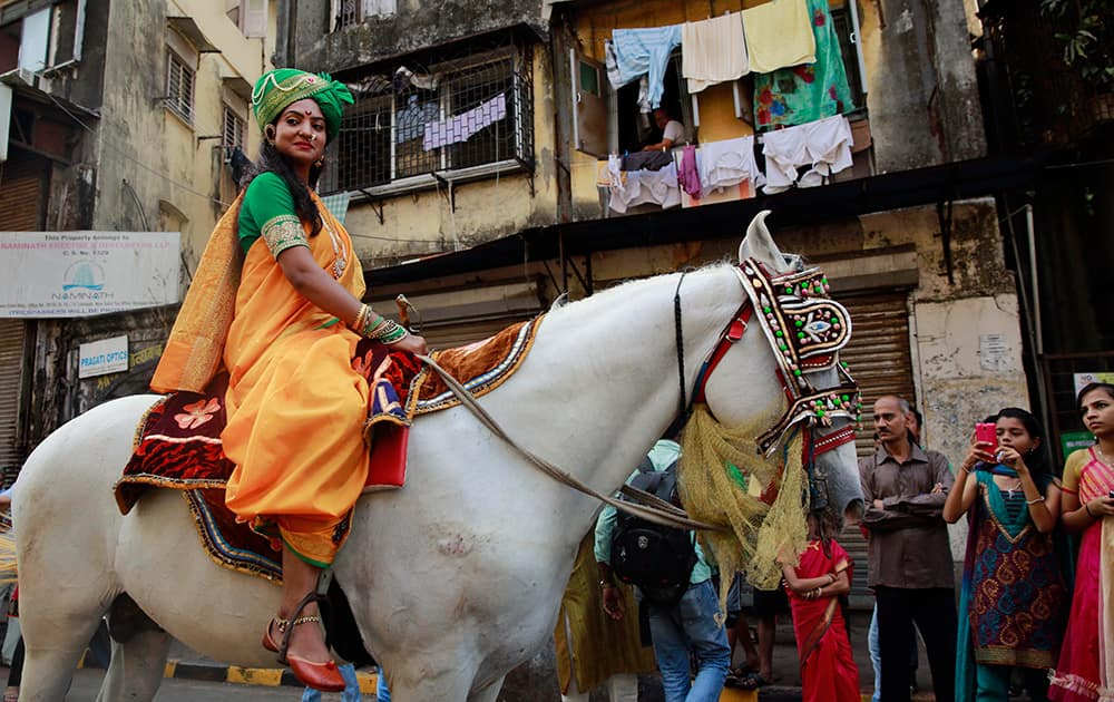 A woman dressed in traditional attire sits on a horse during a procession celebrating `Gudi Padwa`, or the Marathi new year, in Mumbai.