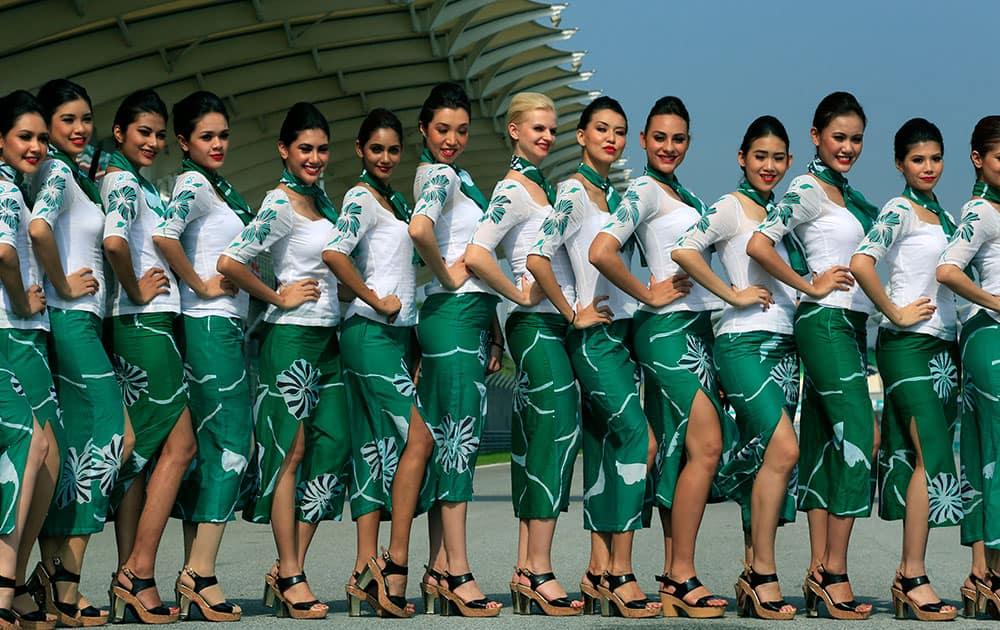 Grid girls pose for photos before the Malaysian Formula One Grand Prix at Sepang International Circuit in Sepang, Malaysia.
