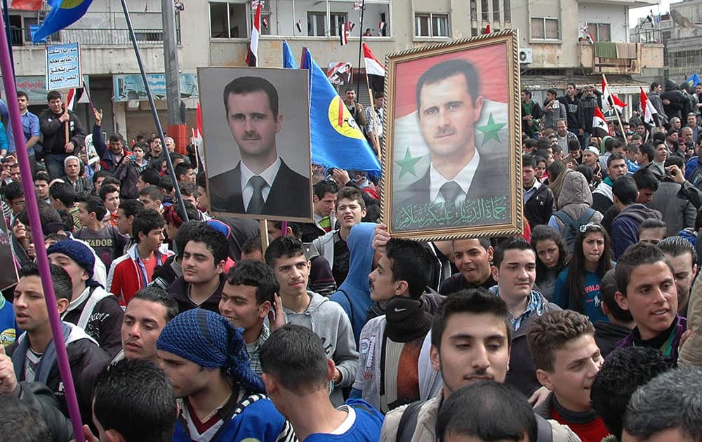 Supporters of Syrian President Bashar Assad, hold up his portraits.