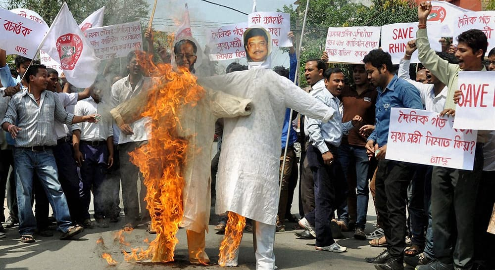 Activists of All Assam Students Union (AASU) burning effigies of Chief Minister of Assam Tarun Gogoi and Forest Minister of Assam Rikibul Hussain in Guwahati.