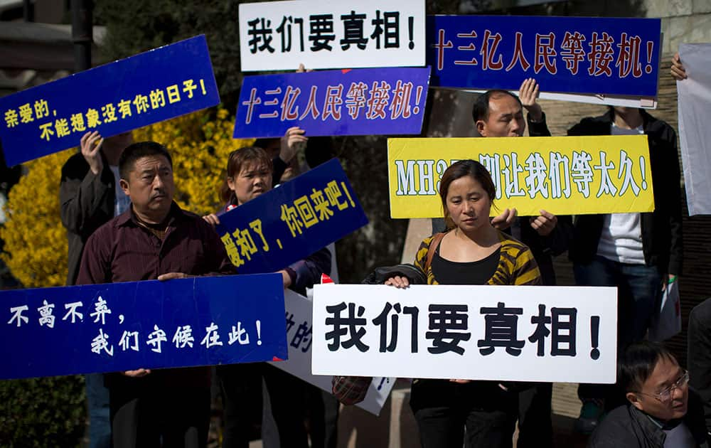 Relatives of Chinese passengers on board Malaysia Airlines Flight 370 hold boards with words, `We want the truth! MH370, do not let us wait too long! My dear, I can not imagine my life without you!` as they stage a protest against the airlines and the Malaysian government at a hotel in Beijing.
