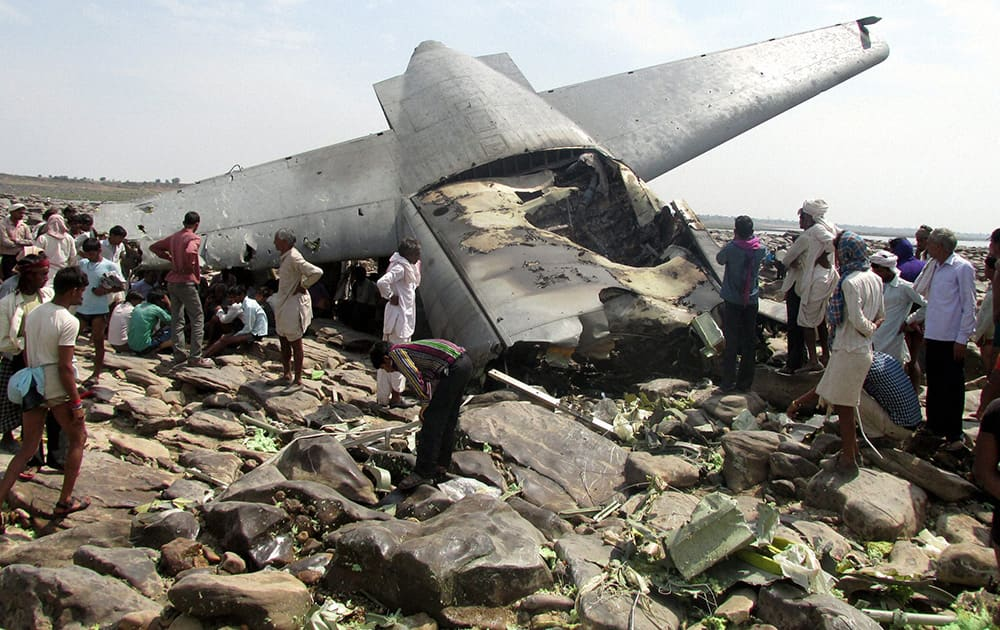 Villagers crowd around the debris of an Indian air force cargo plane that crashed near Karauli village in Madhya Pradesh. C-130J Hercules plane inducted into service just last year crashed during a training mission Friday, killing all five crew members in the latest in a series of accidents that have hit the Indian armed forces.