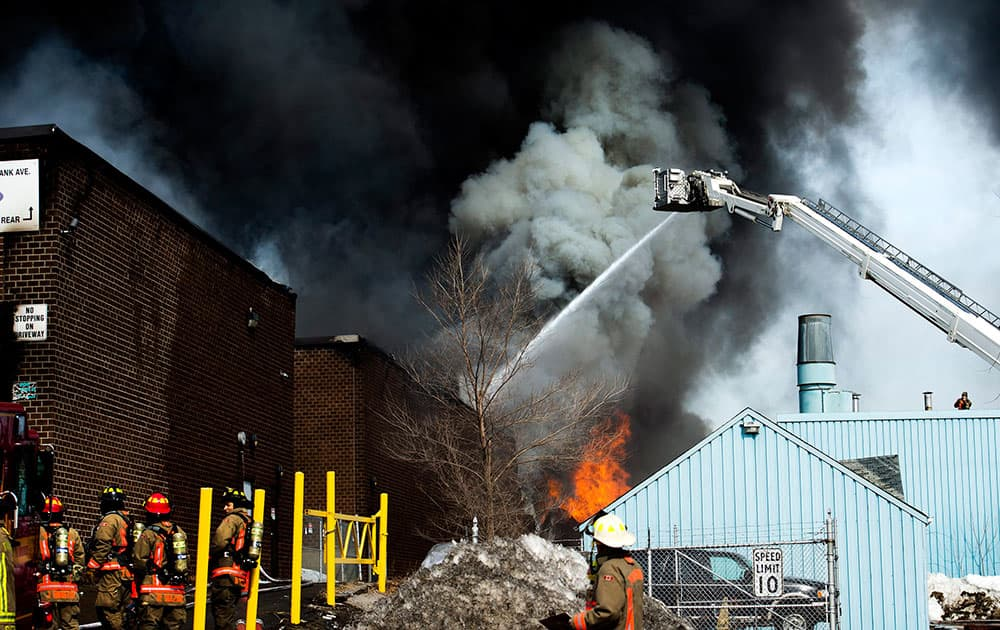 Firefighters battle a six-alarm fire at a mattress factory in Toronto.