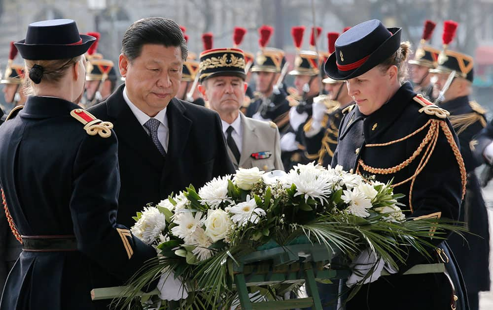 Chinese President Xi Jinping, second left, lays a wreath of flowers at the tomb of the Unknown Sodier in Paris.