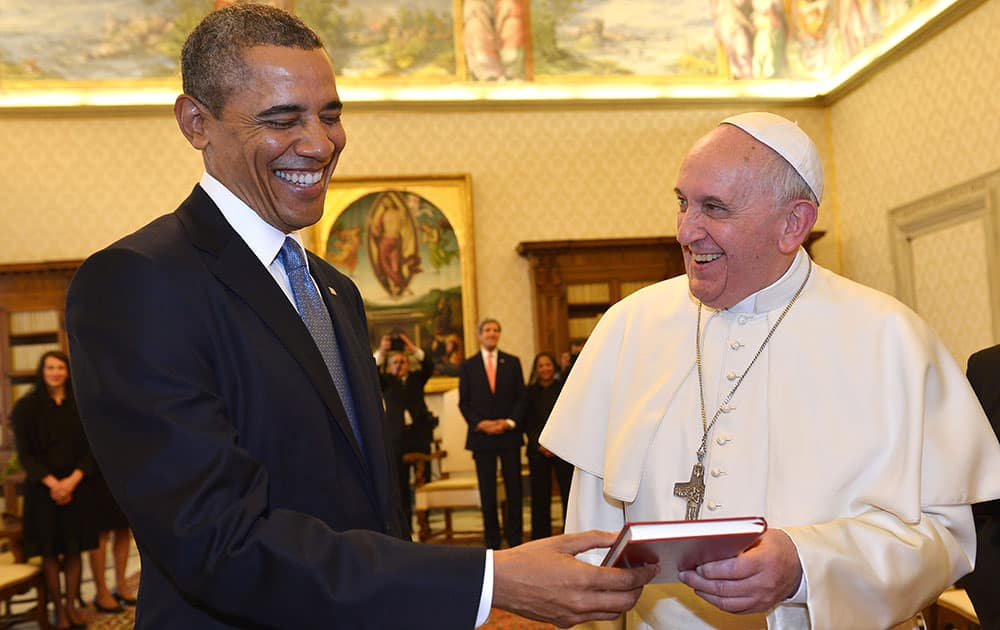 Pope Francis and President Barack Obama smile as they exchange gifts, at the Vatican.