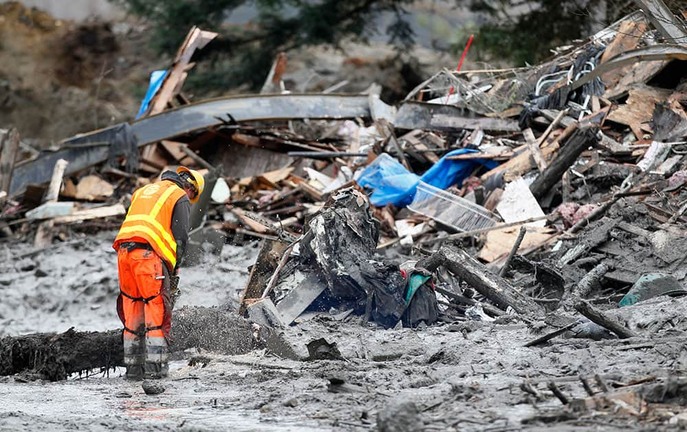 A worker uses a chain saw at the scene of a deadly mudslide that covers the road, in Oso, Wash.