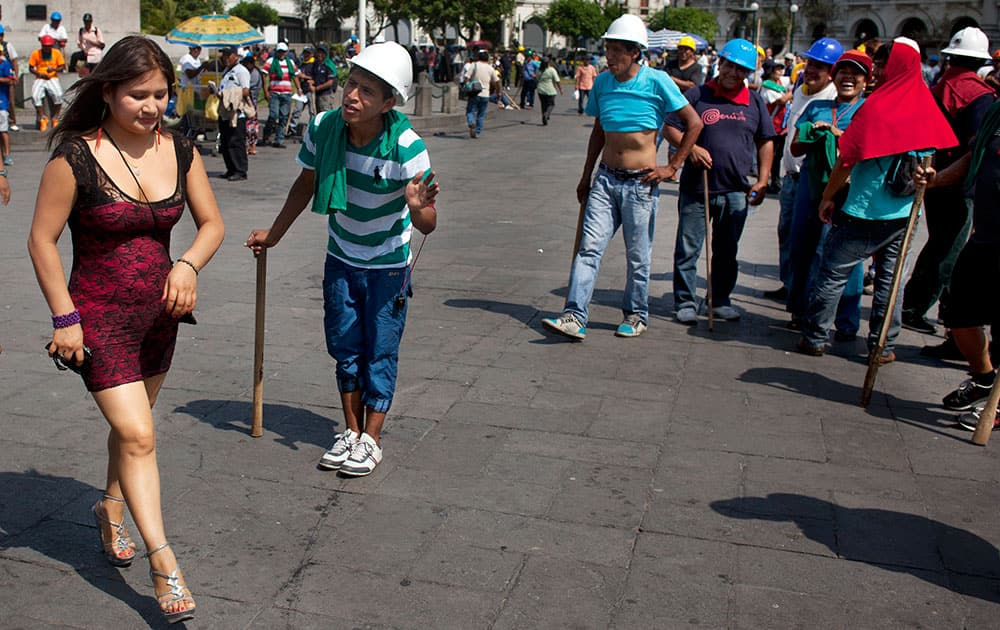 A miner flirts with a woman during a break while protesting in Lima, Peru. Into their seventh day of protesting, miners are asking the government to repeal regulations aimed at formalizing informal miners.