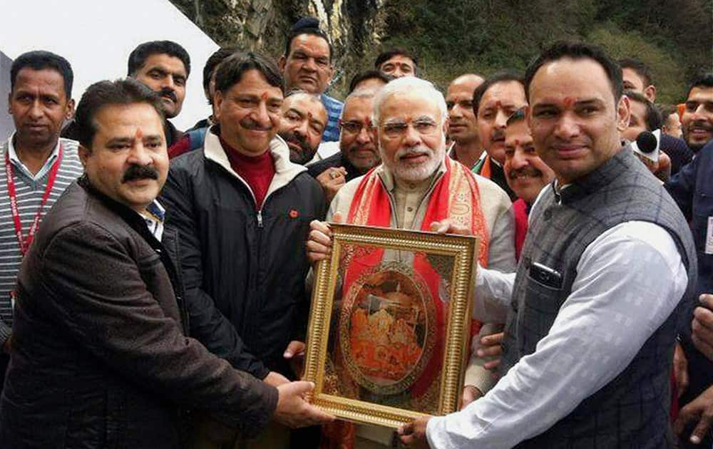 BJPs Prime Ministerial candidate Narendra Modi is presented a portrait of Mata Vaishno Devi during his visit to the shrine in Katra.