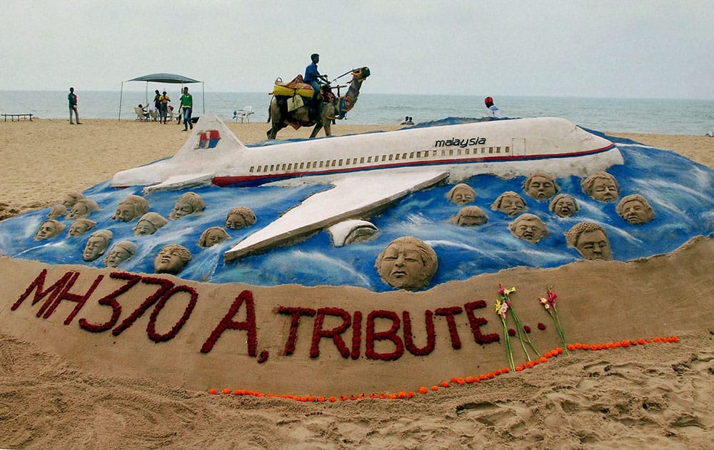 Sand artist Sudarsan Pattnaik creates a sand sculpture to pay tribute to the passenger of Malayasian Airlines MH370, at Puri beach of Odisha.