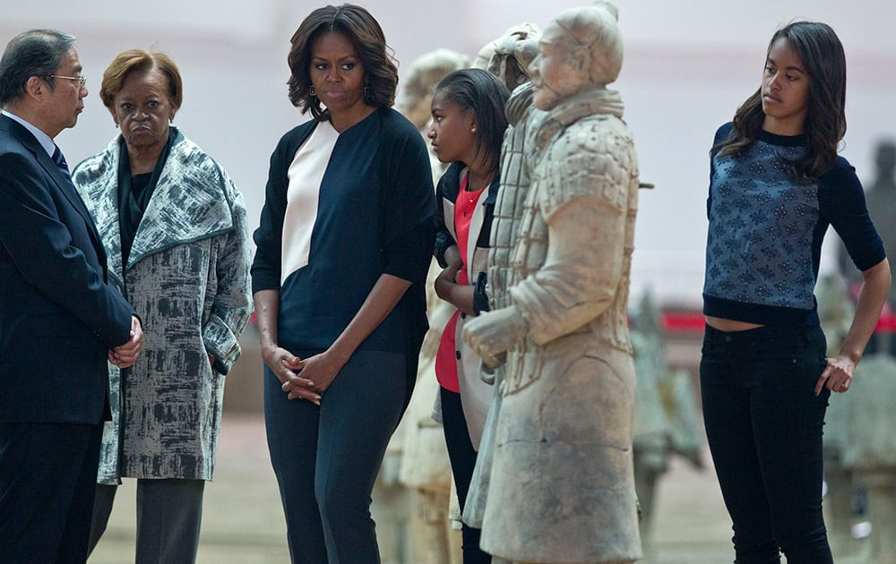 US first lady Michelle Obama looks at a terracotta warrior as she visits Qinshihuang Terracotta Warriors and Horses Museum with her daughters, Malia, right, and Sasha, second right, and her mother, Marian Shields Robinson, second left, in Xi`an, in northwestern China`s Shaanxi province.