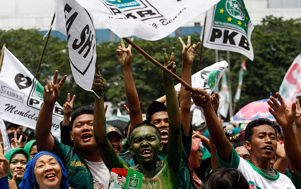 A supporter with his face painted in the color of the National Awakening Party cheers during a campaign rally of the party, led by Indonesian Manpower and Transmigration Minister Muhaimin Iskandar, in Jakarta, Indonesia.