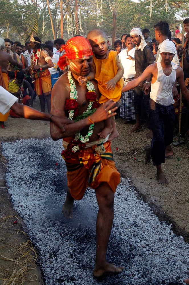 A Hindu devotee carrying a child walk on burning embers in a pit during a traditional Hindu fire festival in Dalla, about 15 kilometers (9 miles) south of Yangon, Myanmar.