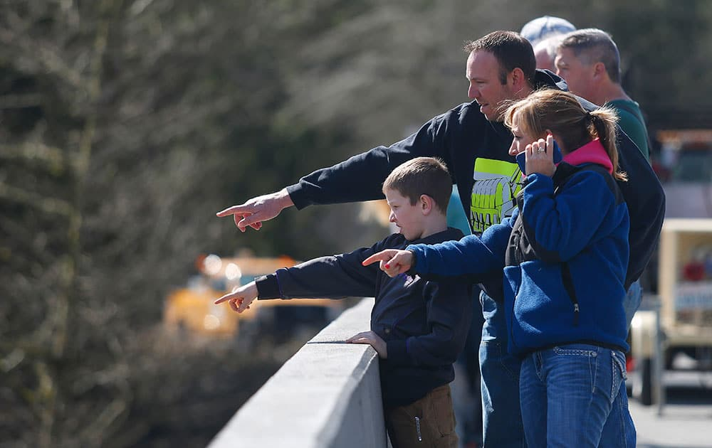 Residents watch as debris comes down the Stillaguamish River from the Whitman Road bridge east of Oso, Wash.