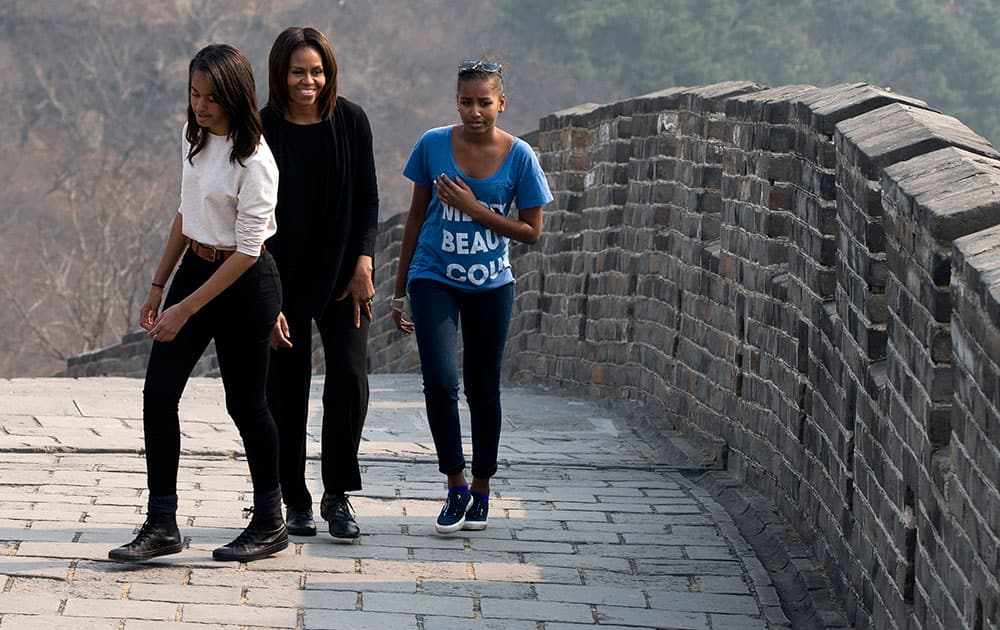 US first lady Michelle Obama walks with her daughters Malia and Sasha as they visit the Mutianyu section of the Great Wall of China in Beijing.