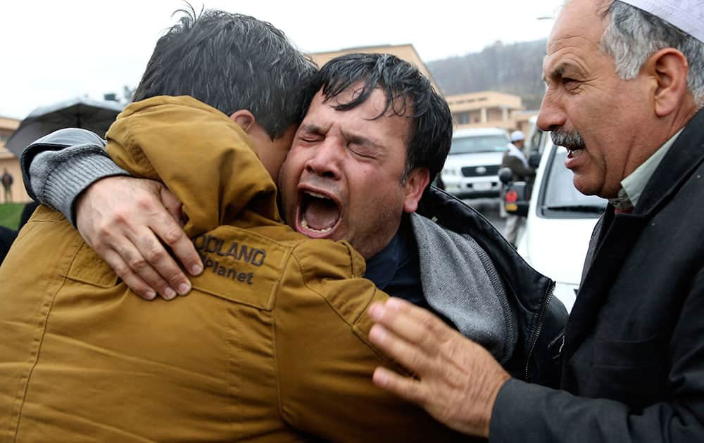 Bashir Ahmad, center, brother of killed Agence France-Press journalist Sardar Ahmad cries during his brother`s funeral ceremony in Kabul, Afghanistan. Sardar, his wife and two of his young children were killed when four gunmen attacked the Serena hotel in Kabul during New Year`s celebrations on March 20, 214. Nine people, including four foreigners were killed during the attack.