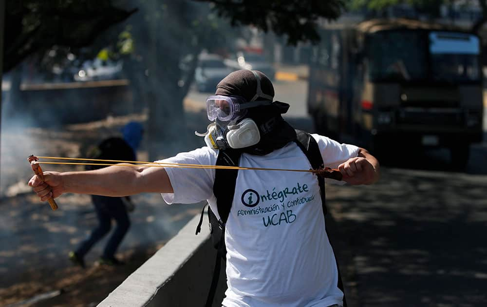 A masked anti-government protester uses a slingshot to shoot marbles at Bolivarian National guards during clashes in Caracas, Venezuela.