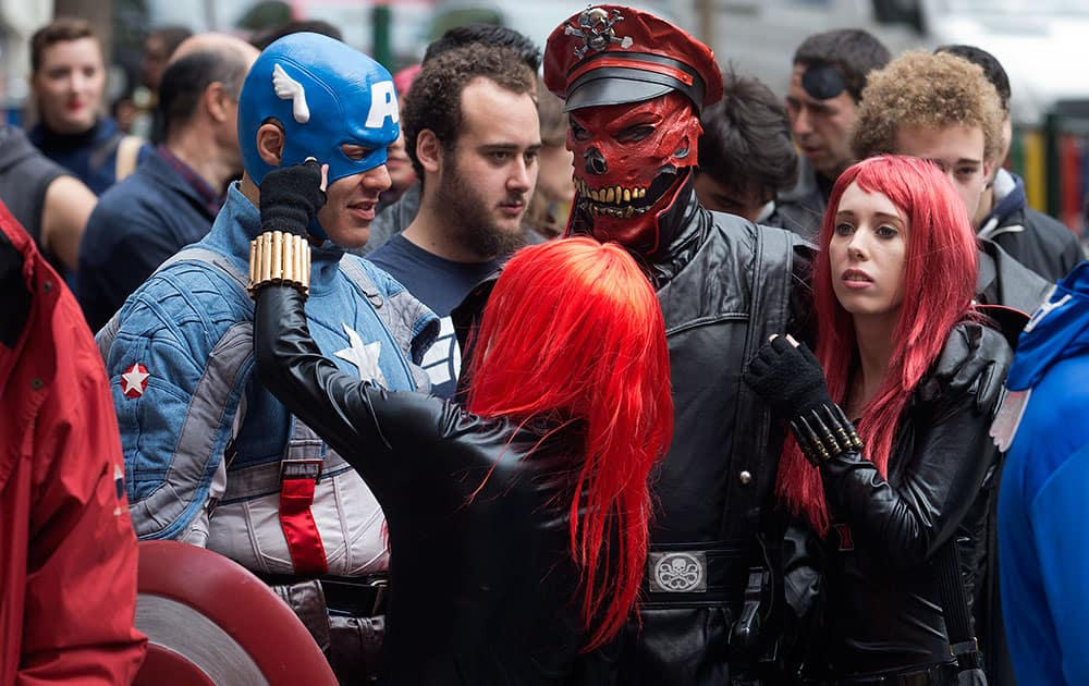 Fans dressed in Captain America character costumes wait in line outside a cinema in Madrid, Spain.