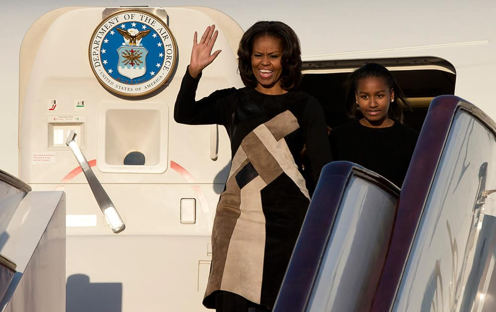US First Lady Michelle Obama gestures as she and her daughter Sasha leave their plane at Capital International Airport in Beijing. Michelle Obama has arrived in Beijing with her mother and daughters to kick off a seven-day, three-city tour where she will focus on education and cultural exchange.