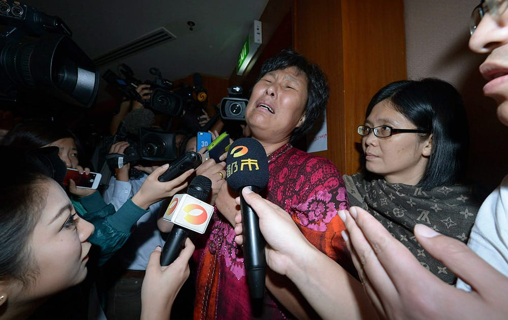A Chinese relative of passengers aboard a missing Malaysia Airlines plane cries as she speaks to journalists at a hotel in Sepang, Malaysia.