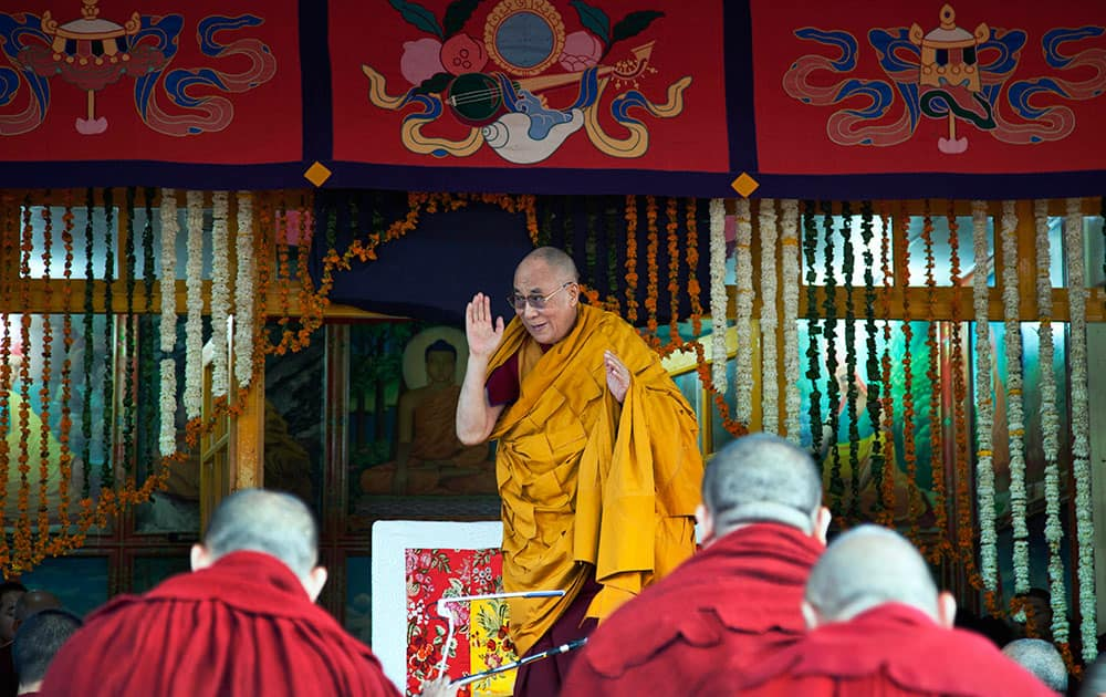 Tibetan spiritual leader the Dalai Lama greets devotees as he arrives to give a religious talk at the Tsuglakhang temple in Dharmsala.