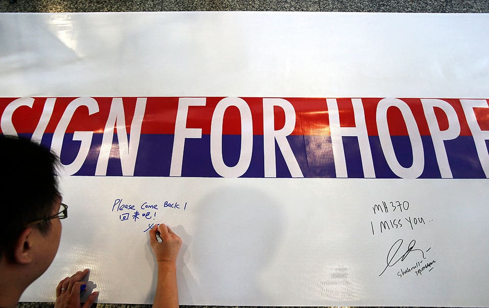 A man writes a message on a 60-meter long banner filled with signatures and well wishes for all involved with the missing Malaysia Airlines jetliner MH370 at the Kuala Lumpur International Airport.