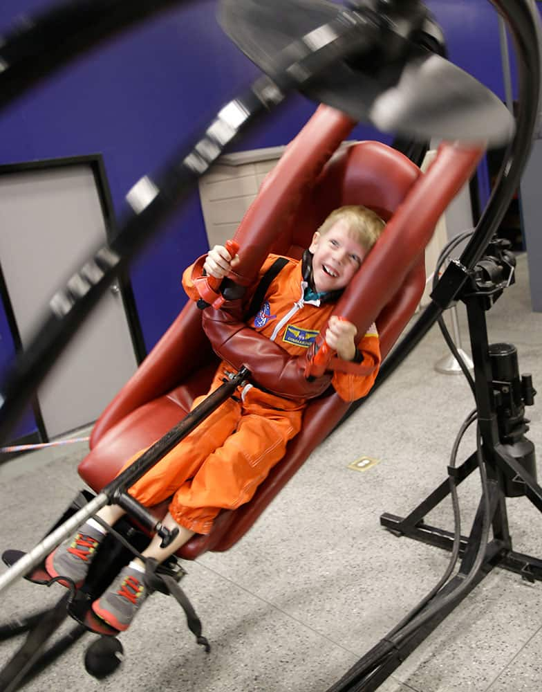 Connor Johnson, 6, of Denver, spins in circles on a multi access trainer in the Astronaut Training Experience, part of the Kennedy Space Center Visitors Complex, in Cape Canaveral, Fla.