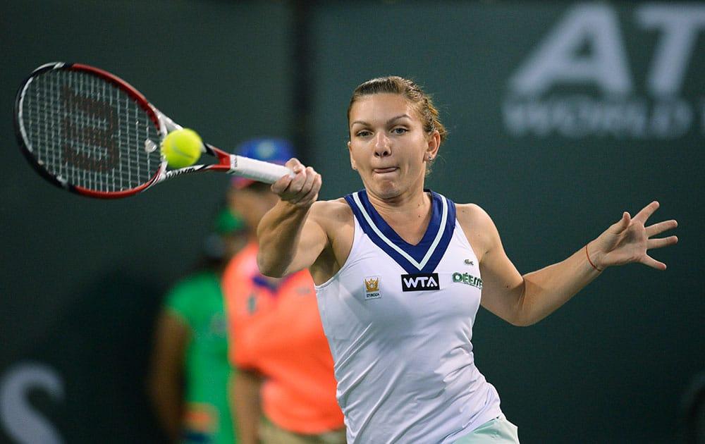 Simona Halep, of Romania, hits to Agnieszka Radwanska, of Poland, during their semifinal match at the BNP Paribas Open tennis tournament.