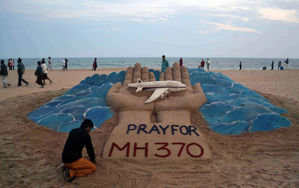 Sand artist Sudarshan Pattnaik creates a sculpture depicting the missing Malaysian Airlines aircraft on the beach in Puri, India.