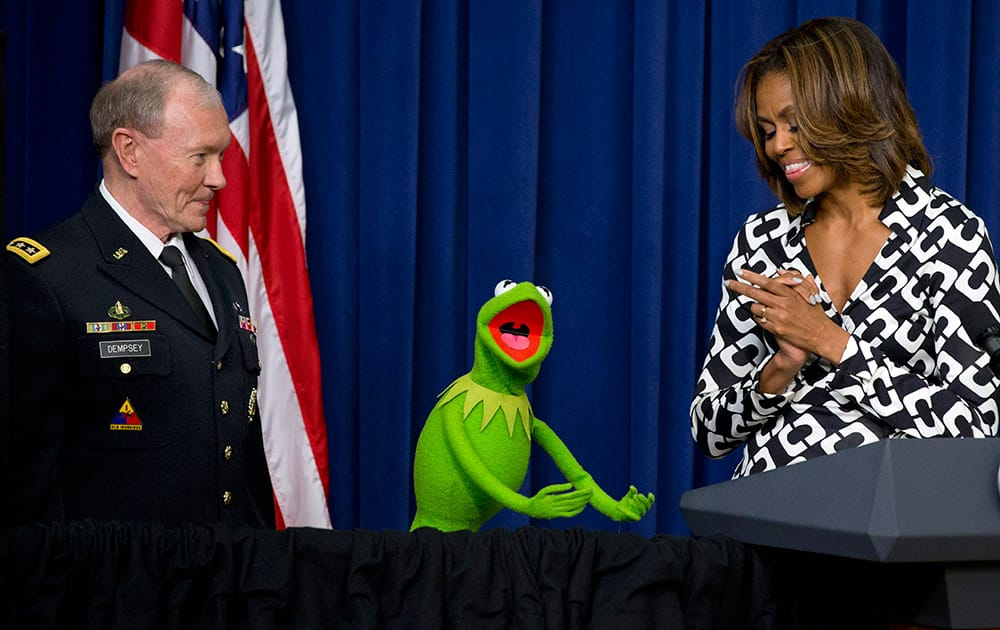 Gen. Martin Dempsey, chairman of the Joint Chiefs of Staff, left, Kermit the Frog, and first lady Michelle Obama, speak to children of military families in the South Court Auditorium of the Eisenhower Executive Office Building on the White House complex, before a screening of Disney's `Muppets Most Wanted` movie as part of the Joining Forces initiative.