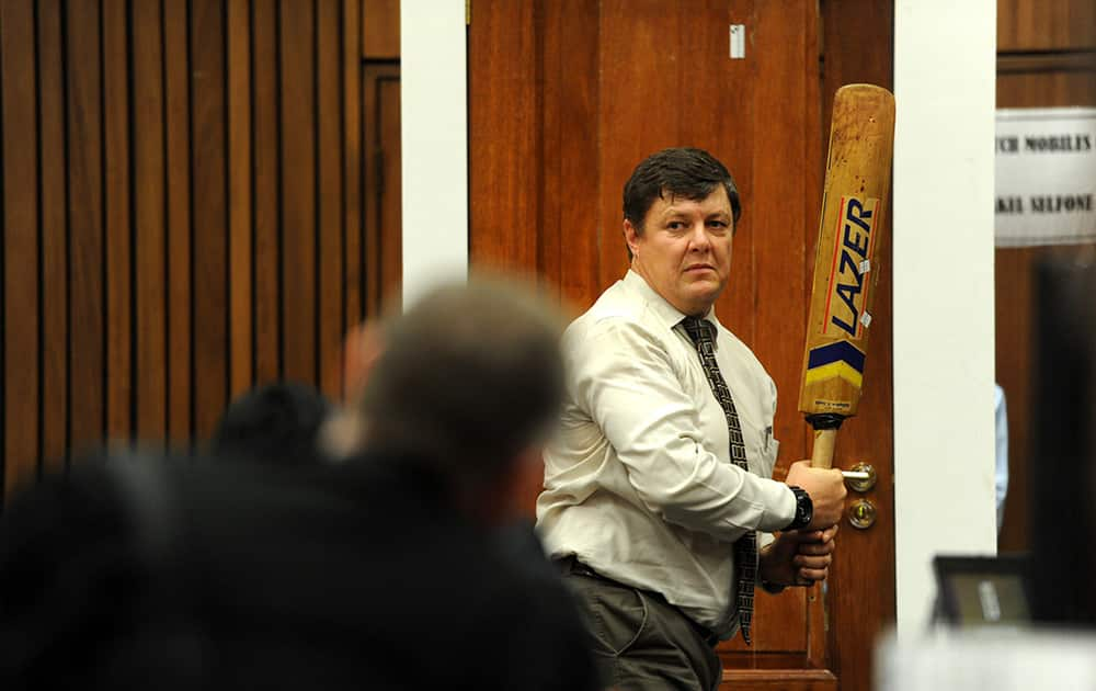 Forensic investigator Johannes Vermeulen, with a cricket bat in hand, demonstrates on a mock-up toilet cubicle, with the door, background, how the door could have been broken down with the bat, during the trial of Oscar Pistorius in court in Pretoria, South Africa.