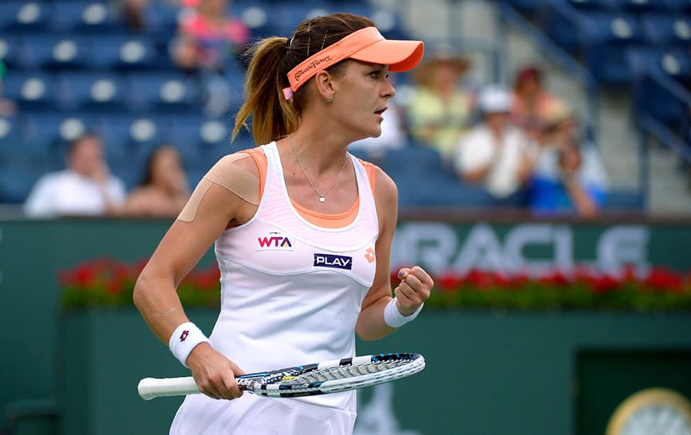 Agnieszka Radwanska, of Poland, pumps her fist after defeating Alize Cornet, of France, 7-5, 6-3, in a fourth round match at the BNP Paribas Open tennis tournament.