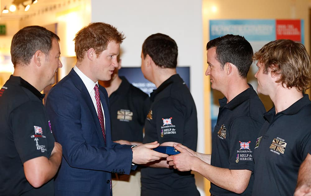 Britain`s Prince Harry, 2nd left, hands medals to members of the Row to Recovery crew, at The River and Rowing Museum, on Henley on Thames, England.