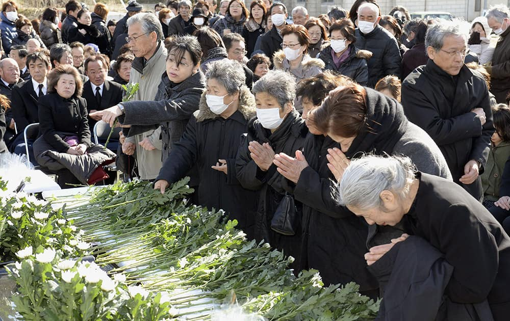 Mourners pray after offering flowers during an unveiling ceremony of a cenotaph in Soma, Fukushima prefecture, northern Japan.