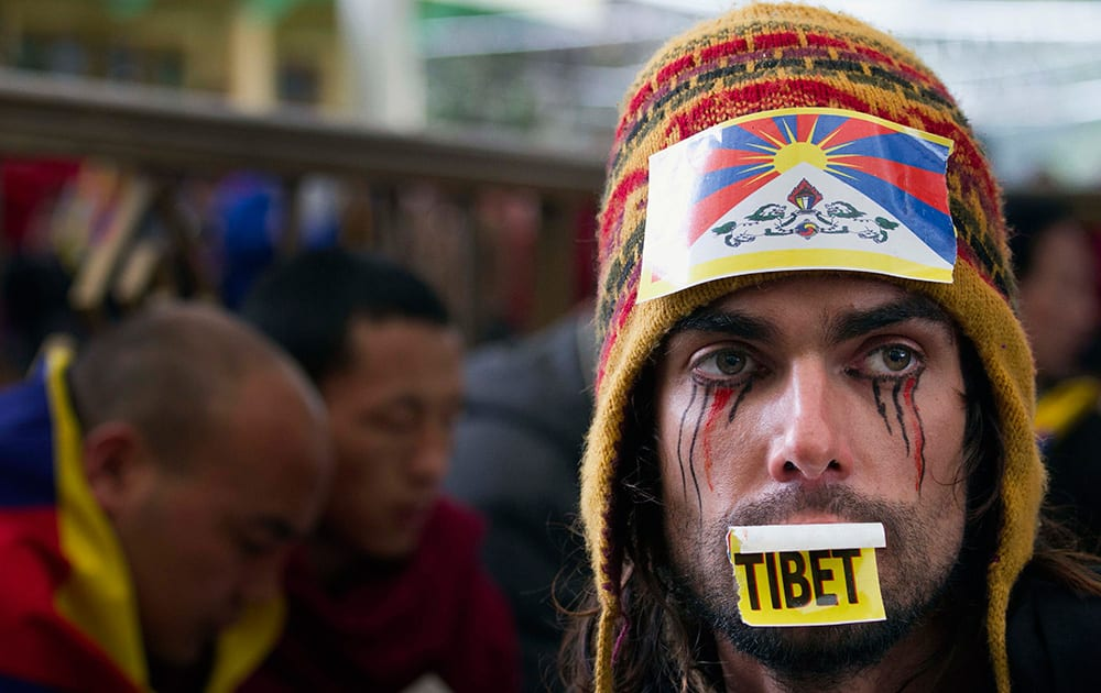 Austrian national Maximilian with a Tibetan flag attached to his hat joins exiled Tibetans at a gathering to mark the 55th anniversary of the failed uprising in the Tibetan capital Lhasa in 1959, in Dharmsala, India.