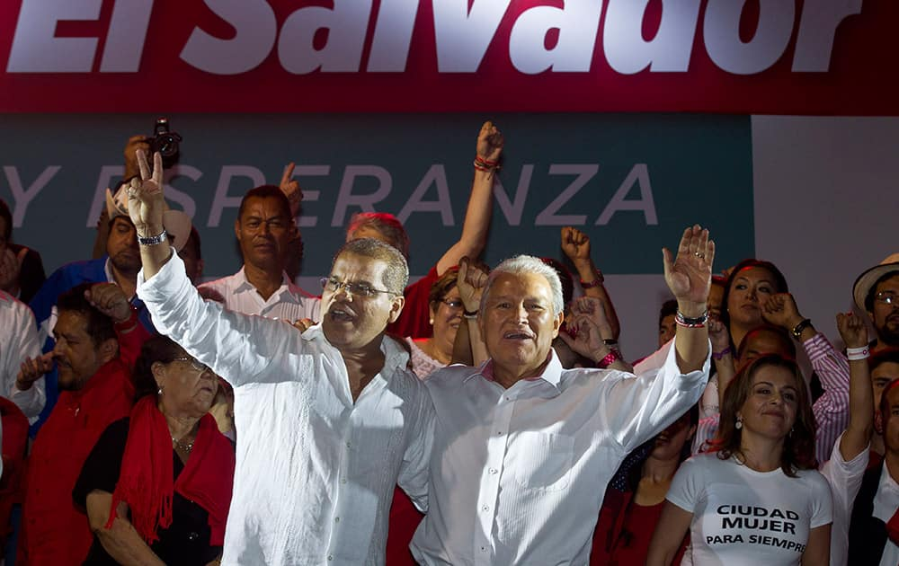 Presidential candidate Salvador Sanchez Ceren, of the ruling Farabundo Marti National Liberation Front (FMLN), right, and vice-presidential candidate Oscar Ortiz wave to supporters as they celebrate after partial results were announced by election authorities in San Salvador, El Salvador.