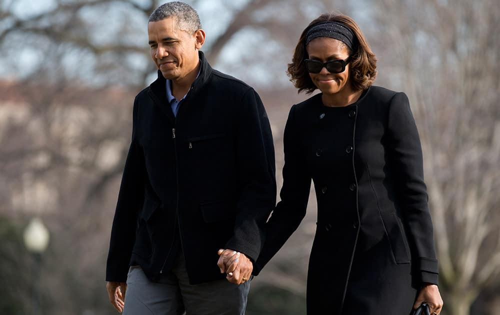 President Barack Obama and first lady Michelle Obama walk hand in hand across the South Lawn to the White House, in Washington, as they arrive from Florida.