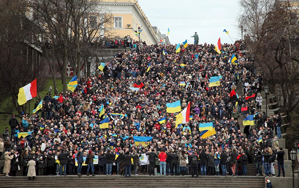 Ukrainians sing the national anthem waving national flags during an anti-war protest on the Potemkin Stairs considered a formal entrance into the city from the direction of the sea and the best known symbol of the Black Sea port of Odessa, Ukraine.