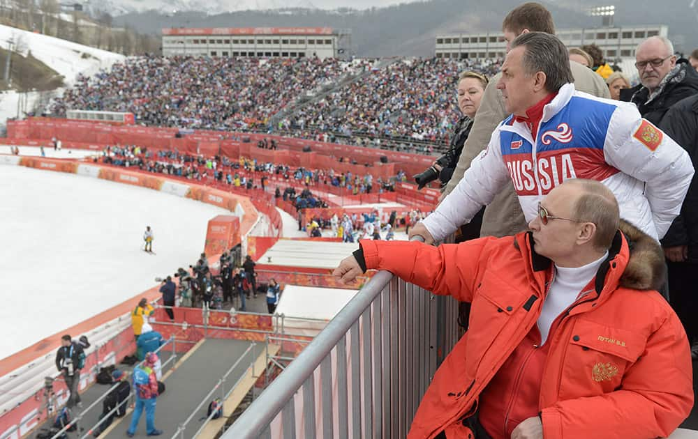 Russian President Vladimir Putin, foreground, watches downhill ski competition of the 2014 Winter Paralympics in Roza Khutor mountain district of Sochi, Russia, as Russia`s sports minister Vitaly Mutko stands behind.
