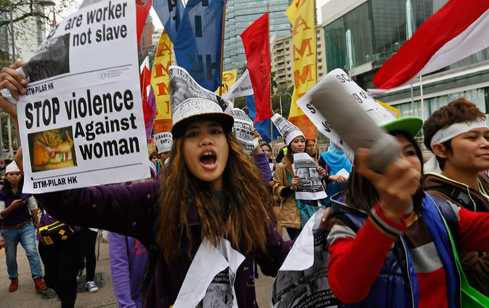 Domestic helpers and their supporters shout slogans during a rally to mark the International Women`s Day in Hong Kong.
